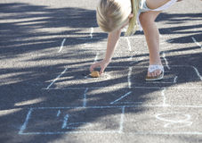 Young girl playing hopscotch Royalty Free Stock Photo