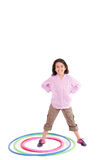 Young girl playing with hula hoop isolated over