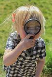 Young girl playing with a magnifying glass royalty free stock photo