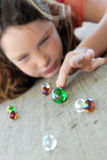 Young girl playing marbles royalty free stock image