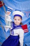 A little girl in sailor clothes. Sea theme stock photos