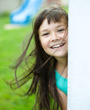 Young girl is playing outdoors. Young cheerful girl is playing outdoors Stock Image