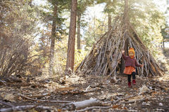 Young girl playing outside hut made of branches in a forest Stock Photos