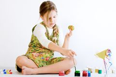 Young girl playing with paint and eggs stock images