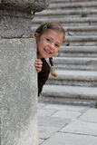 Young girl playing peek a boo. A young girl enjoys playing peek a boo from behind a pillar royalty free stock images