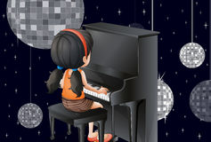 A young girl playing with the piano with disco balls Stock Photos