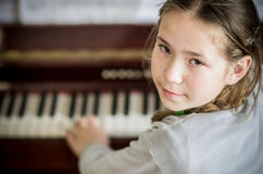 Young girl playing on piano Royalty Free Stock Image