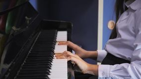 Young Girl Playing Piano in School Class. Schoolgirl on music lessons. Young girl playing a piano stock video