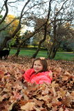 Young girl playing in a pile of leaves. Smiling young girl playing in a pile of Autumn leaves royalty free stock image