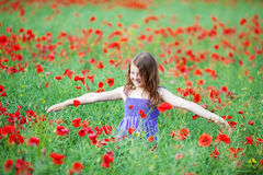 Young girl playing in a poppy field Royalty Free Stock Photos