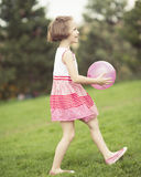 Young girl playing with purple ball in the park Stock Photography