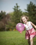 Young girl playing with purple ball in the park Stock Image