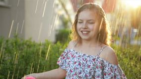 Young girl playing in rain with umbrella. Cutie kid having fun outdoors. stock video footage