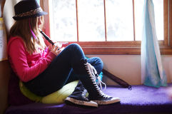 Funky young girl playing the recorder in a colorful window seat. Royalty Free Stock Image