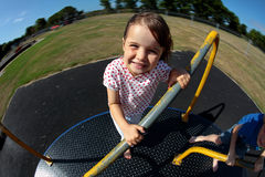Young girl playing on roundabout in sunny park. Happy girl smiling and playing on a roundabout in a sunny family park Royalty Free Stock Photo