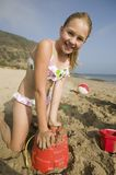 Young Girl Playing in Sand at Beach royalty free stock images