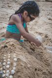 A young girl playing in the sand and building castles. stock photos