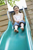 Young Girl Playing On Slide In Park Royalty Free Stock Photos