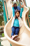 Young Girl Playing On Slide In Playground Royalty Free Stock Images
