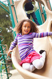 Young Girl Playing On Slide In Playground Stock Photography