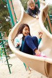 Young Girl Playing On Slide In Playground Stock Photo