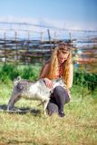 Young girl playing with a small baby goat, rural life. Young girl playing with a small baby goat in the village. country life Royalty Free Stock Images