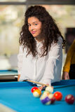 Young girl playing snooker. Girl with curly hair playing billiards Stock Images