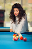 Young girl playing snooker. Girl with curly hair playing billiards Stock Photos