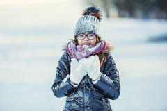 Young girl are playing with snow.Beauty Winter happy Girl Blowing Snow in frosty winter park or outdoors. Stock Image
