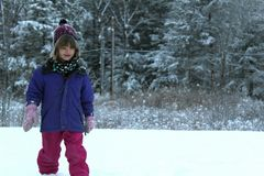 Young girl playing in the snow. Child outside in winter royalty free stock photography