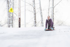 Young girl playing on a snow sled Stock Image