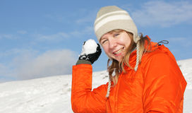 Young girl playing snowball fight. Young pretty girl playing snowball fight on flank of hill stock images