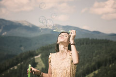 Young girl playing with soap bubbles. Beautiful happy young girl playing with soap bubbles stock photos