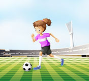 A young girl playing soccer at the field Stock Image