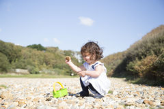 Young girl playing with stones royalty free stock photo