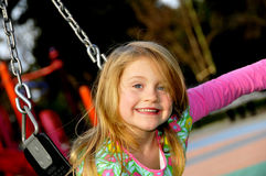 Young Girl Playing on Swing. Young Girl Playing and Having Fun on Playground Swing Stock Photo