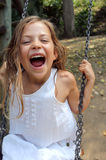 Young girl playing on a swing in a park Stock Photography
