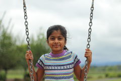 Young girl playing on swing Royalty Free Stock Photos