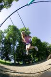 Young girl playing on a swing set at the park Stock Photos