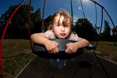 Young girl playing on swing in sunny park. Small child playing on colourful swing in a sunny playground or family park Royalty Free Stock Photography