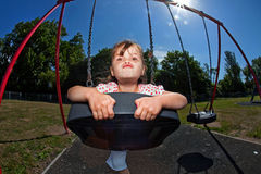 Young girl playing on swing in sunny park royalty free stock photography