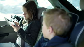 Young girl playing with tablet pc while family traveling to vacation. Two young, cheerful children who are having fun back in the car with playing games on a pad stock video footage