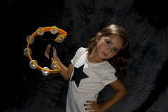 Young girl playing a tambourine Royalty Free Stock Photos