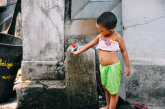Young girl playing with tap in Mandalay. Young girl playing with tap in Mandalay, Myanmar Stock Image