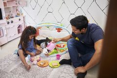 Young girl playing tea party with dad, sitting on the floor, baby brother beside them, elevated view royalty free stock photography