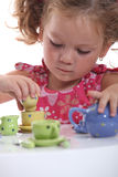 Young girl playing with a tea set Royalty Free Stock Photos