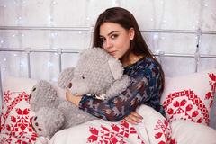 Young girl playing with teddy bear in bed. Girl playing with teddy bear in bed Stock Image