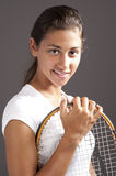 Young girl playing tennis. Studio shot of a young tennis player on the grey background Stock Photo