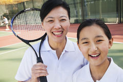 Young girl playing tennis with her coach Stock Photo