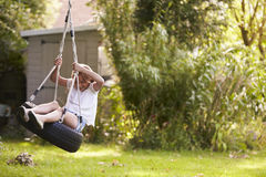 Young Girl Playing On Tire Swing In Garden Royalty Free Stock Images